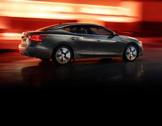 2016 Gun Metallic Nissan Maxima sedan, side view, shown in front of a red background