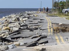 Residents look at Alligator Point road that collapsed during the storm surge from Hurricane Hermine at Alligator Point, Florida on September 2, 2016. Hermine made landfall as a Category 1 hurricane but has weakened back to a tropical storm.