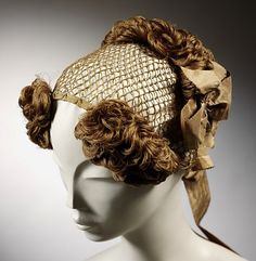 c. 1830's.  The hairnet, left, features a knotted silk mesh, enhanced with clusters of hair curls and a silk bow in the back. It's unclear whether the wearer drew her own hair through the mesh to hide it, wore a cap, or simply counted on the mesh to blend in with the hair beneath.