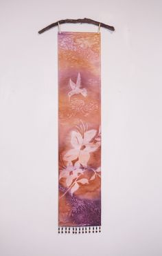 "Purple Copper Hummingbird Floral Wall Art Tapestry. Misty nature silhouettes float over vibrant, watercolor hues in this unique hanging Art Panel. It is hand painted using a textile pigment on silky fabric, resulting in a subtle texture and shimmer. It measures 8"" x 36"", a long narrow painting perfect for small spaces. Delicate loops of ribbon allow it to be hung on a decorative rod or branch, while beaded fringe at the bottom adds a bit of sparkle and weight for a nice drape. Each Art…"