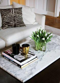 salon avec une ambiance cocooning, canapé blanc, table basse en marbre blanche, avec fleurs