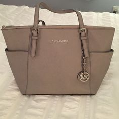 """Michael Kors Jet Set East West Top Zip Tote Pearl Grey/Silver Leather Double handles with 9-1/2"""" drop Top zip closure Silver-tone hardware; 2 side slip pockets; signature plaque at front; detachable logo charm Interior features zip pocket, 4 slip pockets and key fob 15-1/2"""" W x 10"""" H x 4-1/2"""" D - EXCELLENT condition and perfect addition to your collection!  MICHAEL Michael Kors Bags Totes"""