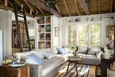 The owner of this New Hampshire lake house furnishes the living room with outdoor finds that can handle wet swimsuits: a wicker sectional sofa from Restoration Hardware and a weather-resistant rug by Dash & Albert. Built-in cubbies store beach blankets and fishing gear, and the ladder leads to a sleeping loft. The walls are painted Strong White by Farrow & Ball.
