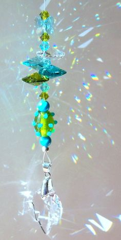 This sparkling sun catcher features a flirty Turquoise Butterfly playing among a Spring color medley. Joining this Swarovski Turquoise Butterfly, Mobiles, Diy Wind Chimes, Hanging Crystals, Rainbow Crafts, Green Theme, Blue Zircon, Stained Glass Art, Sun Catcher, Beads And Wire