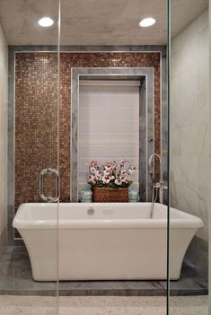 The glossy brown tiles in this luxurious bathroom imitates the appearance of wood, while retaining the lustrous qualities of tiling.