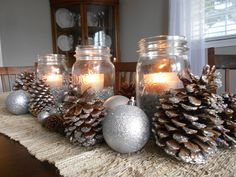 Simple Christmas centerpiece with mason jars, pine cones, and Christmas ornaments. @michaelsstores #Crafts #Christmas