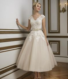 Shown in Oyster/Ivory A 1950's vintage inspired V-neckline tulle tea length ball gown rich in hue. Silk Dupion band accented with a bow cinches the waistline for a figure flattering look. Available colors: Natural/Ivory, Oyster/Ivory
