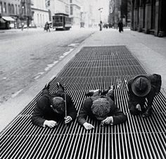 1930, New York.  Scouring for change through a street grate during the Depression.