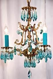 Great way to update a brass chandelier, using turquoise Pebeo Vitrea 160 Glossy Glass Paint (check Amazon) or using the Mod Podge and food coloring technique for the crystals and turquoise paint for the candle holders. If you need to add crystals, flea markets and yard sales are an affordable place to find them (or Amazon has inexpensive acrylic ones).