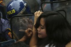 A Filipino protester tries to break through a row of riot police as her group is prevented from marching closer to the U.S. Embassy in Manila to commemorate International Women's Day in the Philippines, on March 8, 2013. Thousands of Filipinos commemorated Women's Day with calls to stop violence against women and children. (AP Photo/Bullit Marquez)