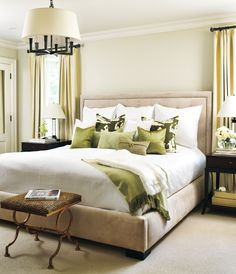 tan & green bedroom design with tan beige tufted bed headboard, Thomas Paul silk green pillows, espresso stained wood nightstands, drum pendant chandelier, soft green silk drapes and soft green paint color. white green bedroom colors.