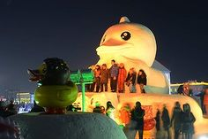 Visitors pose with a snow sculpture of rubber duck during the opening of the 30th Harbin International Ice and Snow Sculpture Festival in Harbin, Heilongjiang province of China.