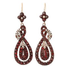 -Victorian coiled snake earrings, 9ct gold backed with silver fronts set with Bohemian garnets and pearls. Suspended from flowers and hung with teardrops. 14K ear wires a likely replacement. 2 1/4 inches. Mid 19th century