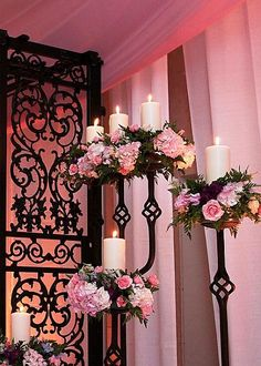 Wrought iron candelabras with pillar candles and soft pink/purple flowers set the background for the ceremony.