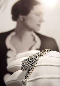 Here, the Duchess of Windsor's Cartier panther bracelet is displayed by a Sotheby's employee in front of a portrait of the Duchess. The fully-articulated bracelet, made by Cartier in 1952, is pavé-set with brilliant- and single-cut diamonds and calibré-cut onyx.  Via Diamonds in the Library.