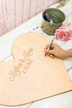 This wooden heart guestbook is personalized with the couples names and wedding date for a custom guestbook that is sure to be treasured for a lifetime. Custom engraved to order in a beautiful natural wood, this wedding or shower guestbook is able to be hung on the wall or displayed on a shelf after the wedding. Have your guests sign their names with a marker (sharpies recommended) and enjoy the unique statement piece that is created on your wedding day. Choose your size to accommodate the…