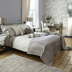 Cream and muted gold bedroom with bold wallpaper accent wall.