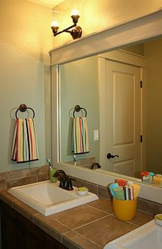 DIY Framing a Bathroom Mirror Tutorial - I really like the sink and the tile.