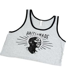 """Ete means """"summer"""" in Creole. The Ete Tank is a unisex jersey tank with an updated, modern fit, featuring a rounded neck designed with superior combed and ring-spun cotton. Deep Heather with Black Trim and the classic vintage Haiti Made Print.  Side-seamed Retail fit Unisex sizing   These particular items are not yet made in Haiti but hopefully soon enough!"""