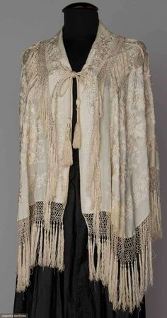 """EMBROIDERED SILK CAPE, CHINA, 1880s Cream silk w/ cream embroidery, fitted back w/ large knotted & tasseled medallion, edged w/ knotted silk fringe, L 22"""", Fringe 8"""", excellent. Diane Gross Collection via Augusta Auctions"""