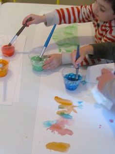 Mixing up bright and colorful M&M paint in preschool