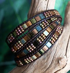 This four wrap bracelet features 5x5mm Miyuki Tila Beads, in gorgeous shades of bronze and iridescent greens, meticulously ladder-stitched on to top