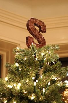 "Initial as a tree topper: ""get a wooden letter and modge podge it with paper to match your Christmas style, wrap it in ribbon, or cover it in glitter"""