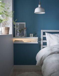 Un comodino fai da te realizzato fissando alla parete, una sopra l'altra, due mensole per quadri MOSSLANDA. Tra le due mensole, una barra luminosa a LED - IKEA