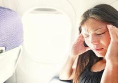 woman-with-headache-on-a-plane-580x387
