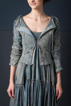 """This cardigan is hand stitched in 100% organic medium-weight cotton jersey with reverse appliqué in our Whispering Rose stencil. Features hook and eye closures down the center front. Measures 22"""" from shoulder. Shown here in Natural Blue Grey. Choose your color below. Please allow four to six weeks for delivery. Wash gently + Hang to dry. Free shipping. Made in the USA."""