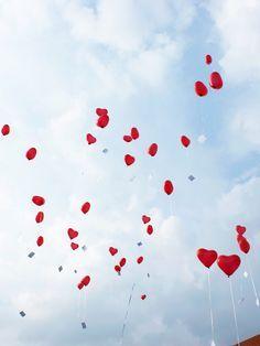 Luftballons in Herzform in den Himmel steigen lassen und sich dabei nur das Beste für das Brautpaar wünschen: schön!