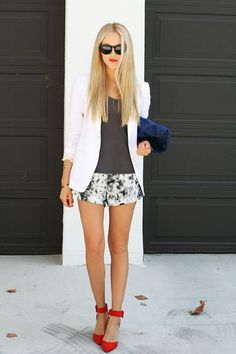 Gorgeous dark grey blouse with white blazer and printed short skirt and royal blue  black mix leather clutch and red high heels ladies pump.