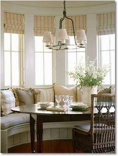 Another bay window with a rounded table.  Love all the light and pillows.