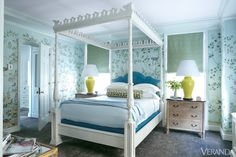 Blue-on-blue bedding and sky-colored hand-painted wallpaper compliment this sun-drenched space. Wallpaper, De Gournay. Canopy bed, Oscar de la Renta Home for Century. Custom lamps. Shades in Fabricut silk. Carpet, Misha Carpet. Trim in Crystal Blue and ceilings in Ballerina Pink, Benjamin Moore. Image originally appeared in the July/August 2012 issue of VERANDA.  INTERIOR DESIGN BY NICK OLSEN