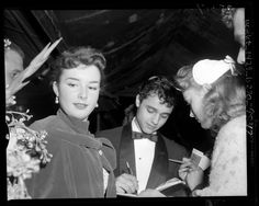 Gigi Perreau and Sal Mineo signing autographs at the premiere of their movie The Man in the Gray Flannel Suit.  c.1956.