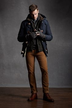 Layered mens winter/fall look, navy coat, black quilted jacket, grey sweater, grey gloves, brown pants