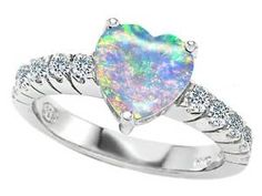 Heart Shape Opal Diamond Engagement Ring - Love is colorful and a gemstone like this is the perfect palette to paint your destiny with this sparkling Heart Shape Opal Diamond Engagement Ring is stamped in 925 Sterling Silver and placed within a Prong setting featuring an Opal Heart cut center stone along with ten small White Round cut accent sides stones on the shoulders of the shank. The Heart Shape Opal Diamond Engagement Ring is Cubic Zirconia and all of the diamonds are simulated…