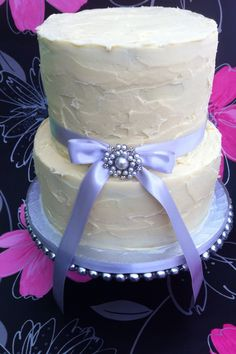 "2 tier wedding cake ( 3 layer lemon drizzle in 10"" & 4 layer chocolate in 8"") covered with white chocolate ganache."