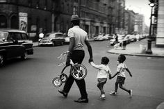 #intimacy in the streets of #Harlem w/Magnum's Leonard Freed. Signed estate-stamped #MAGNUMSquare prints $100. 2 days left. Link in bio. It is 1963 and a man crosses a street in Harlem New York. He must be the father of these children as they follow him in a quick sprint hand in hand though the neighborhood safely crossing the street as a family. Hes a strong young father and the tricycle is not a burden to carry for his children; he carries it as part of his familys togetherness. A…