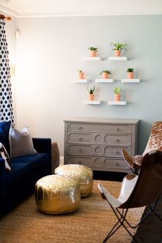 A potted plant wall gallery adds a fun touch to this blue and gold seating area. The mix of cowhide butterfly chairs, gold poufs, and blue couch add the perfect blend of textures and colors.