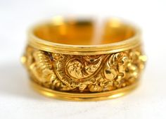 An 18ct gold mourning ring, heavily decorated with a scrolling and foliate design, engraved to t...