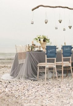 The neutral colors of this beach wedding are perfect for an intimate coastal reception. Hanging decorations, simple table decor, and the sheet table cover has us daydreaming of a breezy overcast day on a quiet stretch of beach along the sea.
