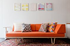 Orange sofa with colorful pillows and wall art hanging above.