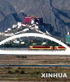 A train chugs on the railway bridge across Lhasa River with the Potala Palace in the background in Lhasa,