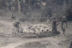 North Nigeria, small group of adult females piling pots onto pile of sticks for firing. Wearing cloths and head-scarves. Rural setting, trees in background. Medium: Gelatin silver print.