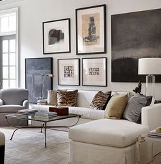 Chic living room design in white, beige, gray, and black with a gallery wall of modern artwork and animal print pillows - Living Room Ideas & Decor