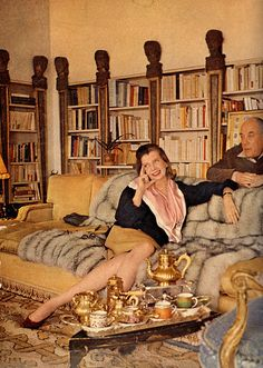 The Baron and Baroness de Rothschild in their library. Note the carved heads at the top of the pilasters and the fur throw on the sofa. And the warmth of the honey golden color everywhere, down to the gold tea service.