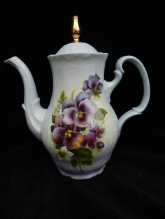 This is a beautiful Bernadette Coffee Pot is designed with a purple Pansy design. The coffee pot is accented with hand painted shading in blues