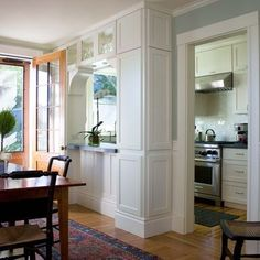 """galley kitchen: small but charming...column has integrated cabinets, """"transom window""""-style glass upper cabinets"""