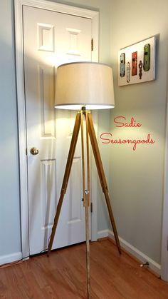 Take a vintage surveyor's tripod and turn it into a stunning floor lamp for pennies compared to trendy home decor store versions with this awesome DIY tutorial! High-end mid-century modern style for a flea market price. #SadieSeasongoods